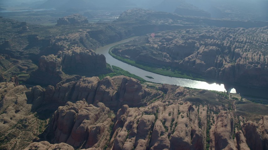 Fly over desert rock formations toward Colorado River, Moab, Utah Aerial Stock Footage | AX138_048
