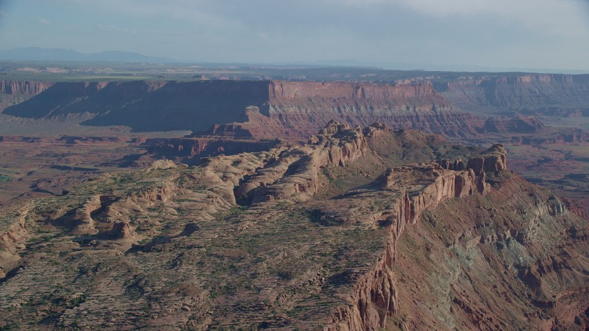 6K stock footage aerial video of rock formations overlooking a wide canyon with a view of mesas, Moab, Utah Aerial Stock Footage | AX138_053