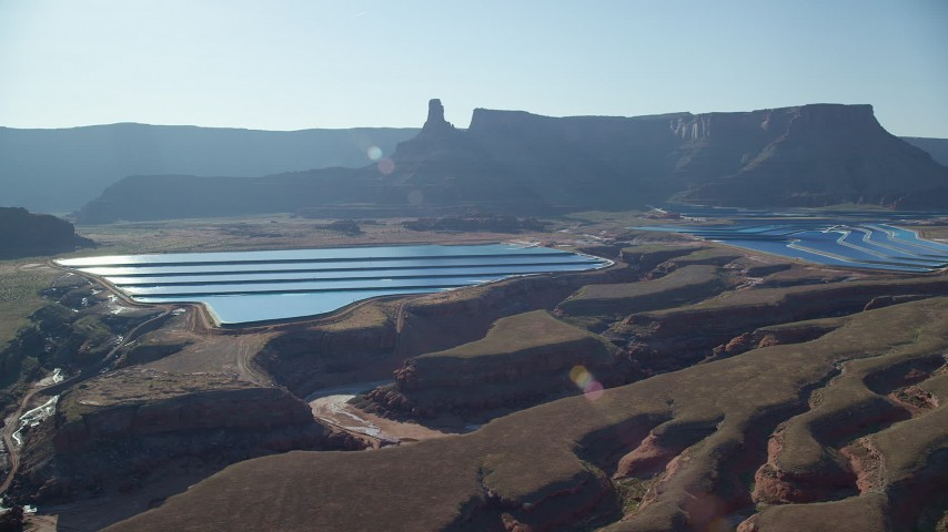 Sun shining on potash ponds with butte and mesa behind it, Moab, Utah Aerial Stock Footage | AX138_062
