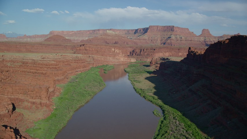 Follow Colorado River in Goose Neck Area with mesas in the distance, Meander Canyon, Canyonlands National Park, Utah Aerial Stock Footage | AX138_087