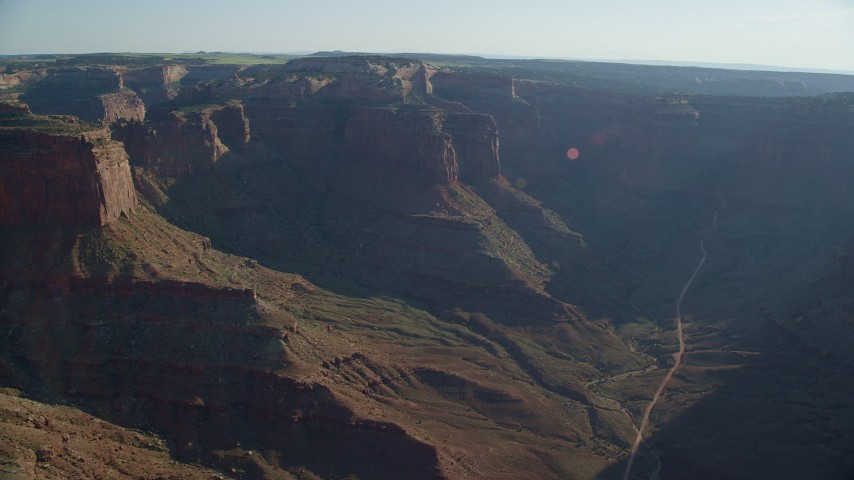 6K stock footage aerial video of tall mesas and a road through Shafer Canyon in Canyonlands National Park, Utah Aerial Stock Footage | AX138_120