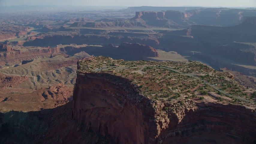 6K stock footage aerial video approach and tilt to cars parked on Dead Horse Point Overlook with view of Canyonlands National Park, Utah Aerial Stock Footage | AX138_157