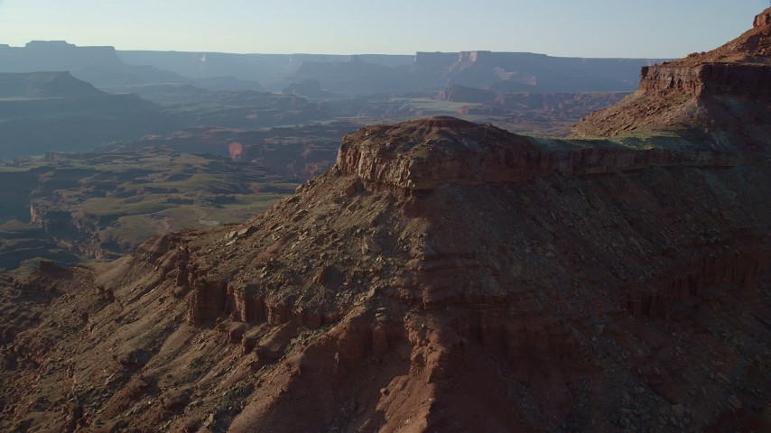 6K stock footage aerial video of a reverse view of a small domed butte with Canyonlands National Park in the background, Utah Aerial Stock Footage | AX138_187