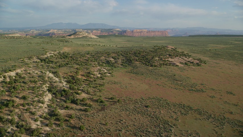 6K stock footage aerial video of approaching rocky dome hill, mesas in background, Moab, Utah Aerial Stock Footage | AX138_241