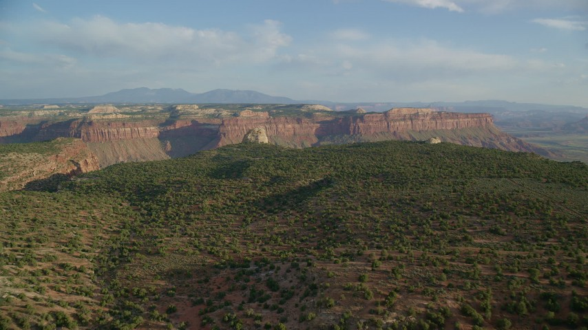 6K stock footage aerial video of approaching rock overlooking a canyon, mesas in the background, Moab, Utah Aerial Stock Footage | AX138_245