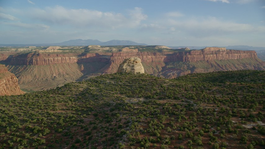 6K stock footage aerial video of approaching a rock overlooking a canyon, mesas in the background in Moab, Utah Aerial Stock Footage | AX138_246