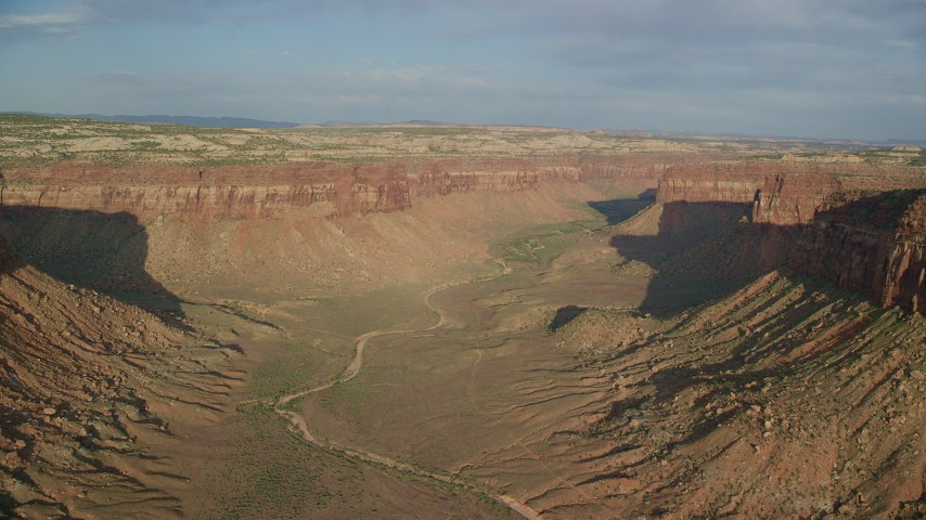 Following dry riverbed through wide desert canyon, Moab, Utah Aerial Stock Footage | AX138_250