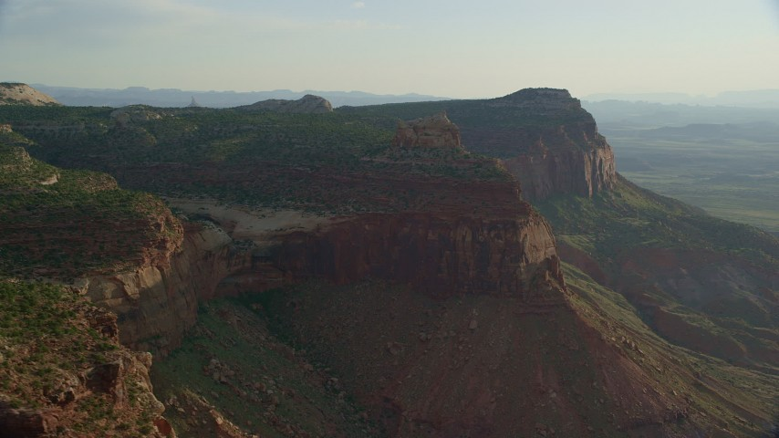 6K stock footage aerial video of flying by a mesa, overlooking a hazy canyon, Moab, Utah Aerial Stock Footage | AX138_251