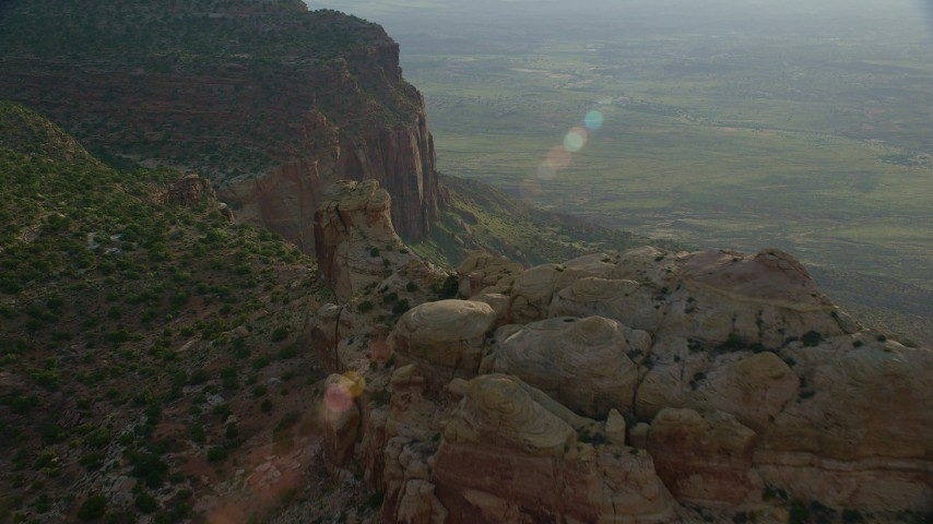 Flying over rock formations and mesa cliffs, overlooking hazy valley, Moab, Utah Aerial Stock Footage | AX138_253