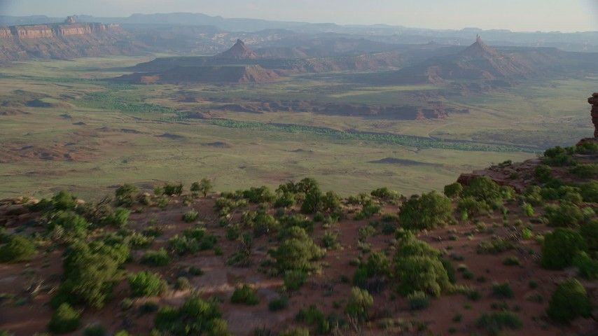 Reveal South Six-Shooter Peak, North Six-Shooter Peak, hazy valley, Moab, Utah Aerial Stock Footage AX138_257