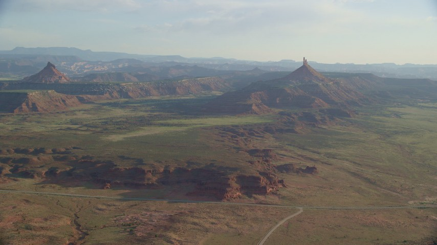 6K stock footage aerial video slowly approach North Six-Shooter Peak, South Six-Shooter Peak in hazy valley, Moab, Utah Aerial Stock Footage | AX138_261