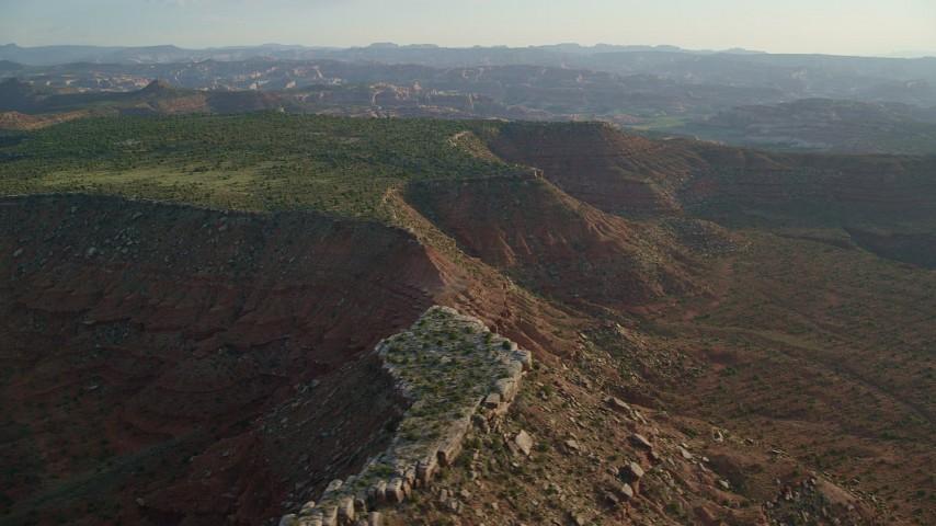 6K stock footage aerial video of flying by desert mesa, hazy valley in background, Moab, Utah Aerial Stock Footage   AX138_275