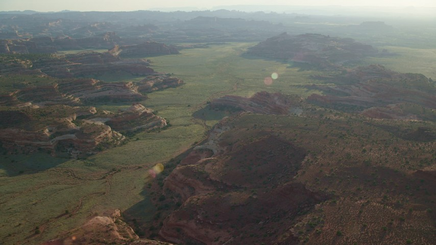 6K stock footage aerial video of flying by desert rock formations in a hazy valley, Canyonlands National Park, Utah Aerial Stock Footage | AX138_277