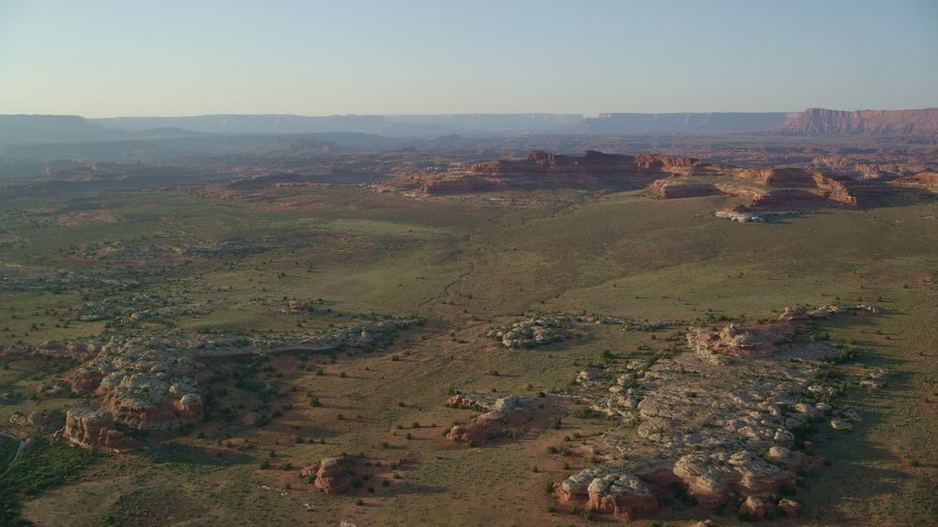 Flying by desert rock formations, distant tall cliffs, Canyonlands National Park, Utah Aerial Stock Footage | AX138_285