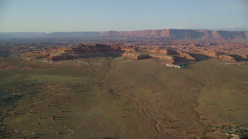 6K stock footage aerial video of a wide view of desert rock formations and distant cliffs, Canyonlands National Park, Utah Aerial Stock Footage | AX138_286