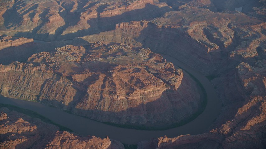 6K stock footage aerial video of the river at sunset at the bottom of The Loop West, Meander Canyon, Canyonlands National Park, Utah Aerial Stock Footage | AX138_318