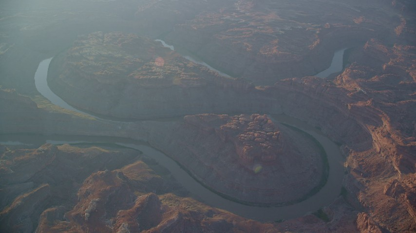 The Loop West, The Loop East, Colorado River, Meander Canyon, hazy, Canyonlands National Park, Utah, sunset Aerial Stock Footage | AX138_330