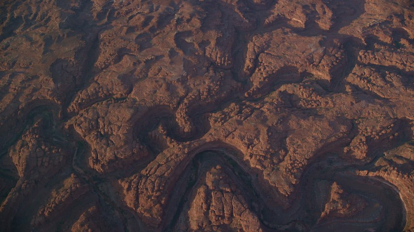 6K stock footage aerial video bird's eye view of dry riverbeds through rocky canyons, Canyonlands National Park, Utah, sunset Aerial Stock Footage | AX138_336