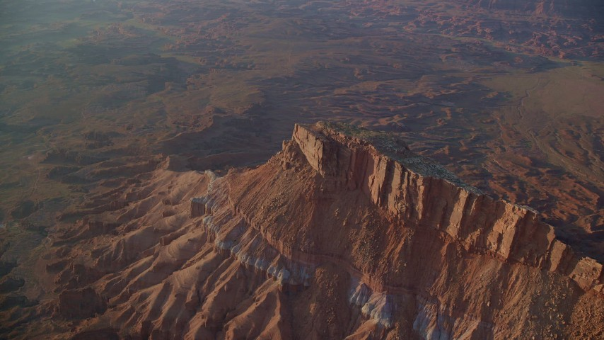 Flying by butte, Lockhart Canyon, hazy, Moab, Utah, sunset Aerial Stock Footage | AX138_342