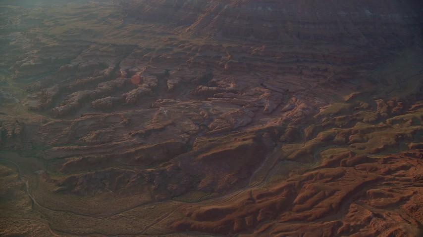 Flying by rock formations, box canyons, hazy Lockhart Canyon, Moab, Utah, sunset Aerial Stock Footage | AX138_347