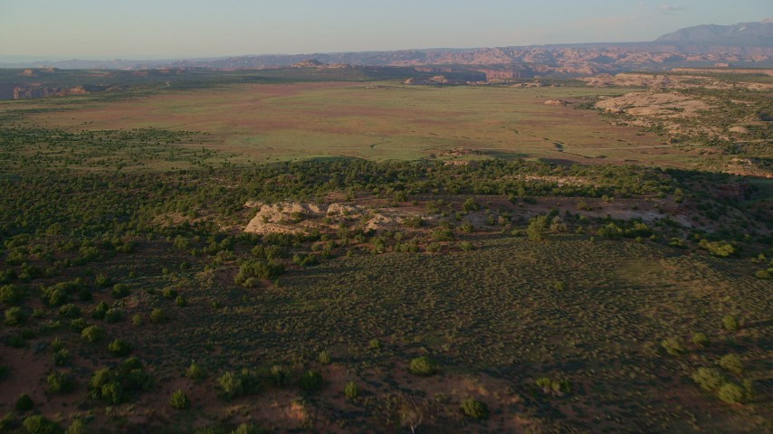 6K stock footage aerial video of flying over rock formation, revealing Hatch Point Road, Moab, Utah, sunset Aerial Stock Footage | AX138_353