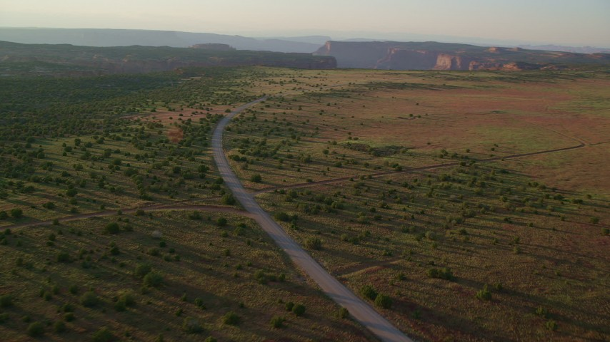 Flying by Hatch Point Road, dirt road intersection, Moab, Utah, sunset Aerial Stock Footage | AX138_354