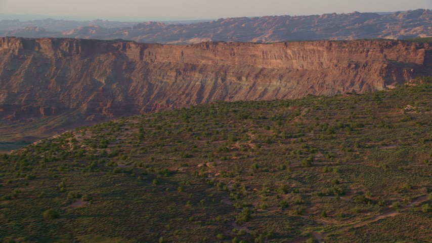 6K stock footage aerial video of panning across canyon, seen from Hatch Point, Moab, Utah, sunset Aerial Stock Footage | AX138_360