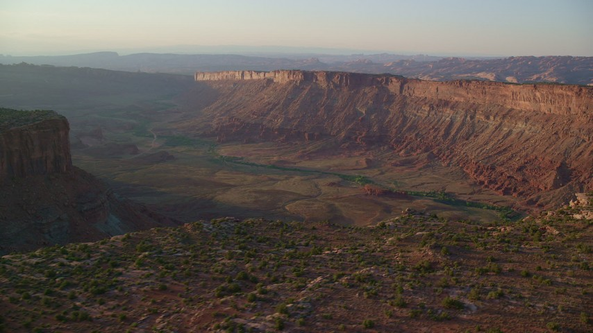 6K stock footage aerial video of flying by a wide desert canyon, Moab, Utah, sunset Aerial Stock Footage | AX138_361