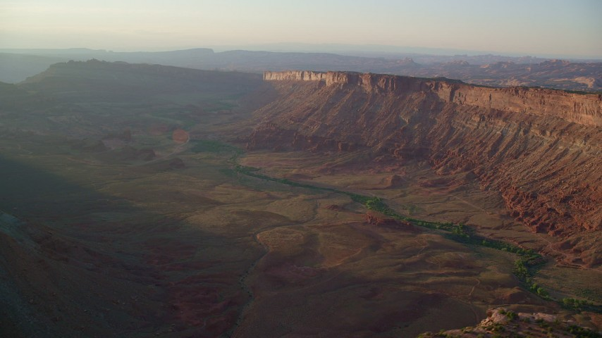 6K stock footage aerial video of passing by a wide hazy desert canyon, Moab, Utah, sunset Aerial Stock Footage   AX138_362