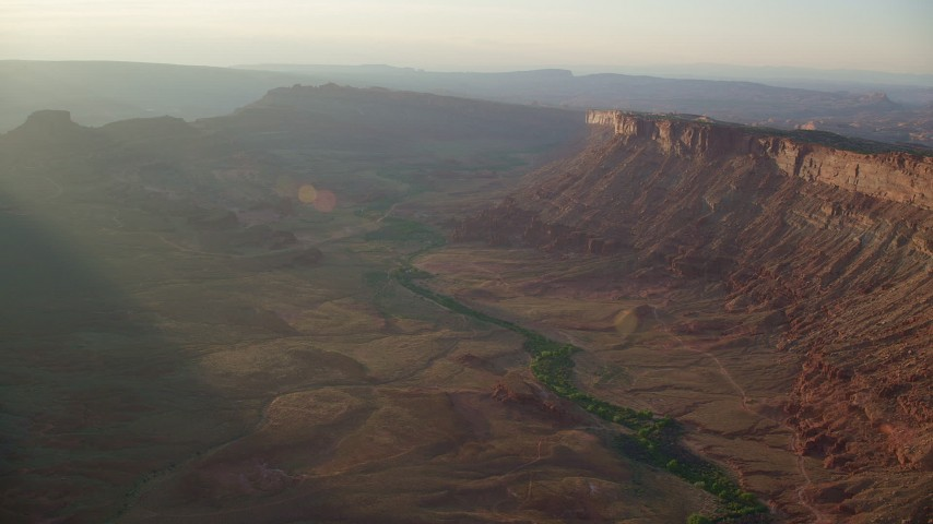 Flying by hazy desert canyon, Moab, Utah, sunset Aerial Stock Footage | AX138_363