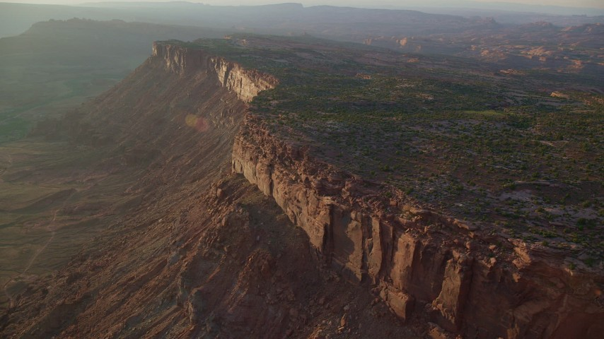 6K stock footage aerial video of flying by canyon cliffs and hazy valley, Moab, Utah, sunset Aerial Stock Footage | AX138_364