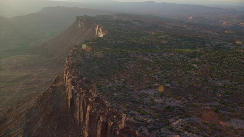 6K stock footage aerial video of passing by canyon cliffs and hazy valley, Moab, Utah, sunset Aerial Stock Footage | AX138_365