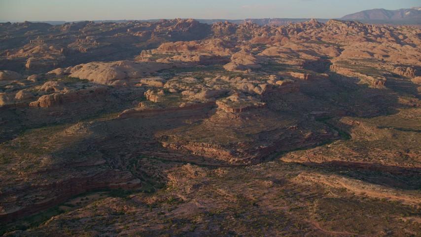 6K stock footage aerial video of flying toward desert rock formations, Moab, Utah, sunset Aerial Stock Footage | AX138_367
