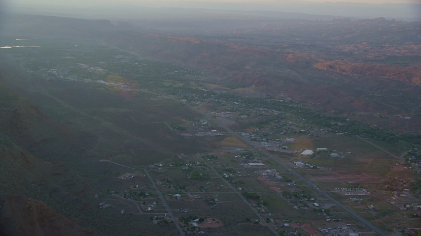 6K stock footage aerial video of flying by the small desert town of Moab, Utah, sunset Aerial Stock Footage | AX138_375