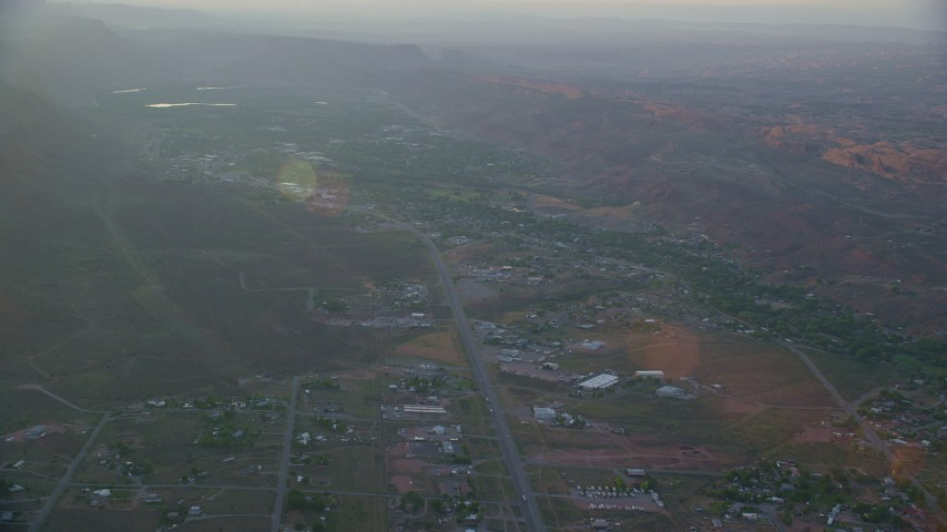 6K stock footage aerial video of passing by a small town, Moab, Utah, sunset Aerial Stock Footage | AX138_376