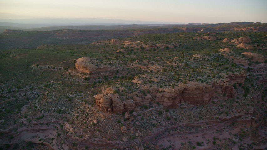 Approaching desert rock formations, Moab, Utah, sunset Aerial Stock Footage | AX138_381