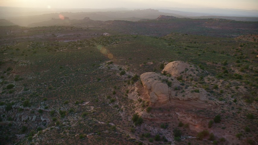 Flying by rock formations, desert valley, Moab, Utah, sunset Aerial Stock Footage | AX138_382