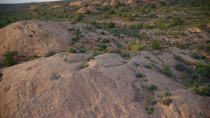 6K stock footage aerial video of flying over and past rock formations in a desert valley, Moab, Utah, sunset Aerial Stock Footage | AX138_386