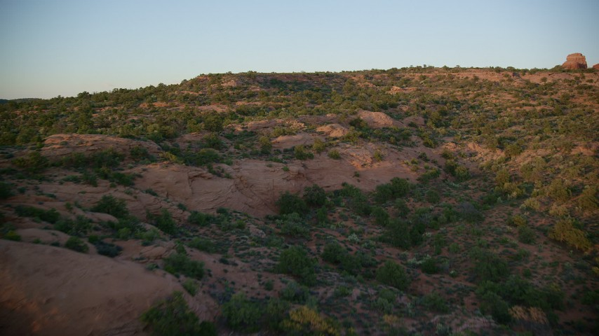 6K stock footage aerial video of a low flight over rock formations, desert vegetation, Moab, Utah, sunset Aerial Stock Footage   AX138_389