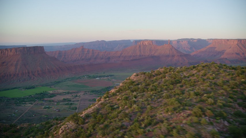 6K stock footage aerial video of flying over hill, revealing Castle Valley and buttes in distance, Moab, Utah, sunset Aerial Stock Footage | AX138_392