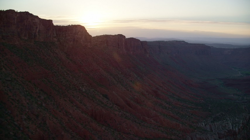 Flying by the sun setting behind mesa cliffs, Moab, Utah, sunset Aerial Stock Footage | AX138_394