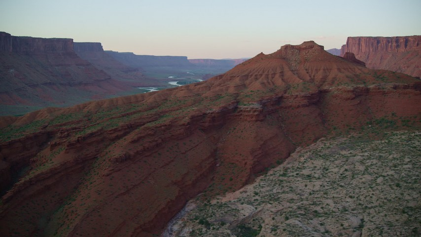 6K stock footage aerial video of flying by side of butte, reveal Colorado River, Moab, Utah, sunset Aerial Stock Footage | AX138_397
