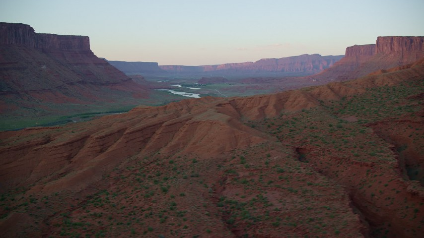 Flying by Colorado River, mesas, beyond rock formations, Moab, Utah, sunset Aerial Stock Footage | AX138_398