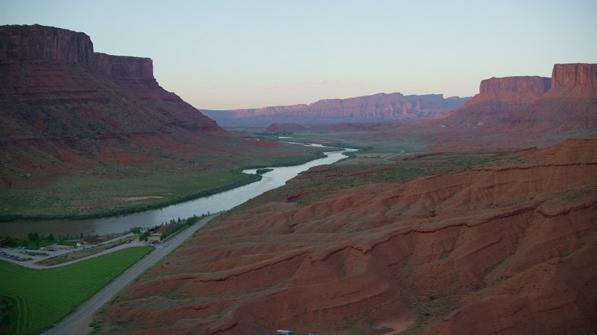 6K stock footage aerial video of passing the Colorado River with view of distant mesas, revealing Red Cliffs Lodge, Moab, Utah, sunset Aerial Stock Footage | AX138_399