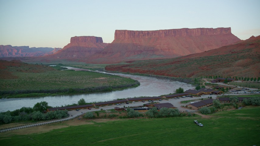 6K aerial stock footage video of a view of Parriott Mesa and the Colorado River from Red Cliffs Lodge, Moab, Utah, sunset Aerial Stock Footage AX138_401 | Axiom Images