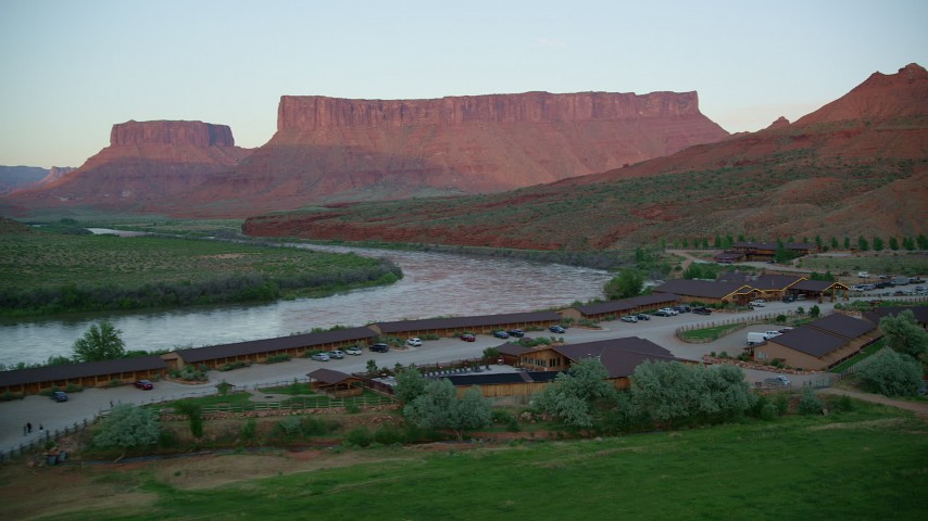 Approaching Red Cliffs Lodge, Colorado River, Parriott Mesa, Moab, Utah, sunset Aerial Stock Footage AX138_402