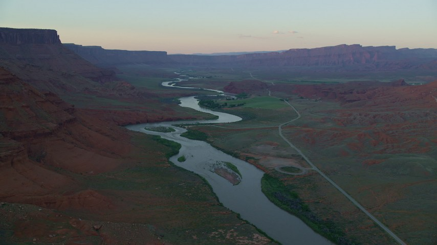 Pan left by Colorado River, State Route 128, mesas, Moab, Utah, sunset Aerial Stock Footage | AX138_405