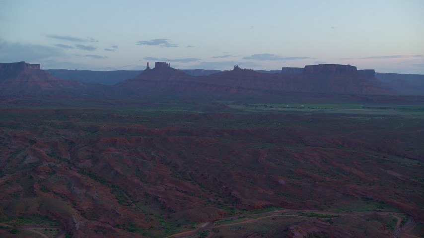 Flying by desert buttes, across valley, Moab, Utah, twilight Aerial Stock Footage | AX138_449