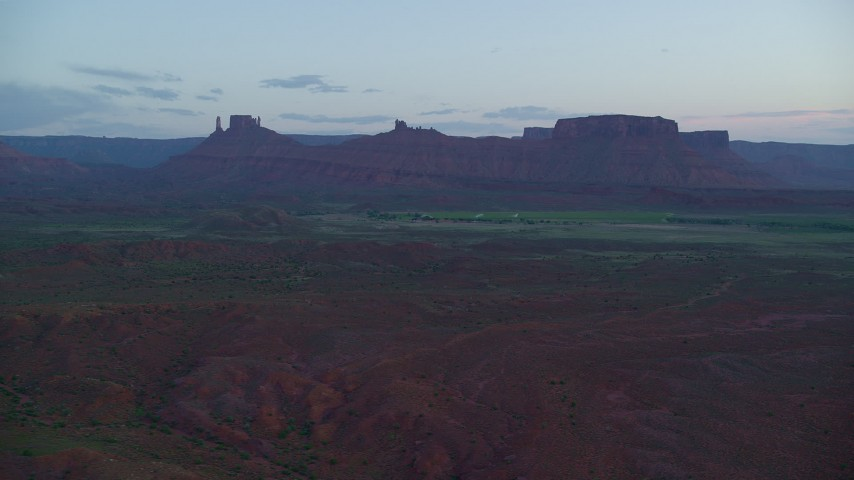 Flying by desert buttes, across valley, Moab, Utah, twilight Aerial Stock Footage | AX138_450