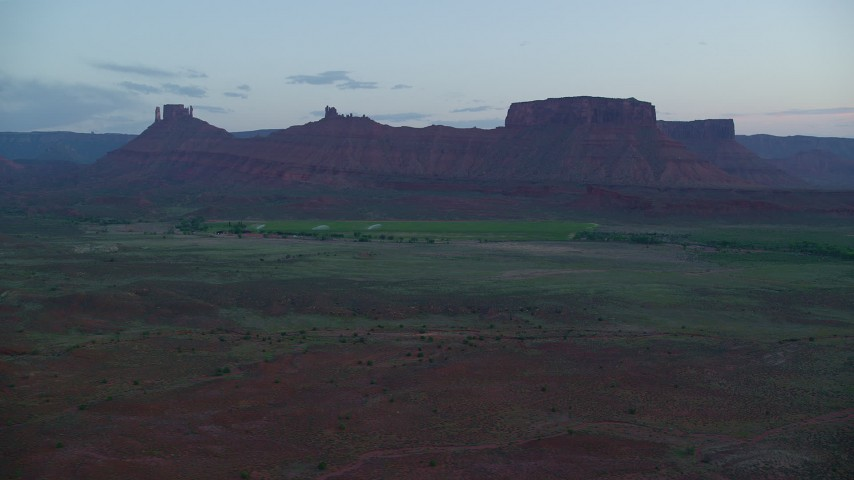 Flying by desert buttes, across valley, Moab, Utah, twilight Aerial Stock Footage | AX138_452
